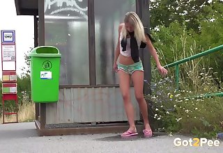 Shameless titillating exhibitionist Claudia Macc is peeing near a bus stop